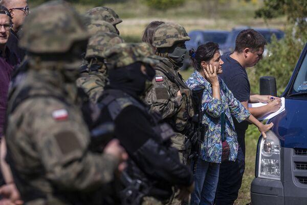 Polští a běloruští pohraničníci s pomocí tlumočníků a aktivistů se snaží komunikovat se skupinou migrantů, pravděpodobně z Afghánistánu, ve vesnici Usnarz-Gorny v Polsku - Sputnik Česká republika