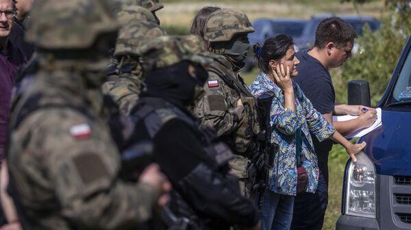 Польские и белорусские пограничники рядом с переводчиками и активистами, пытающимися общаться с группой мигрантов, предположительно из Афганистана, в селе Уснарз-Горный, Польша - Sputnik Česká republika
