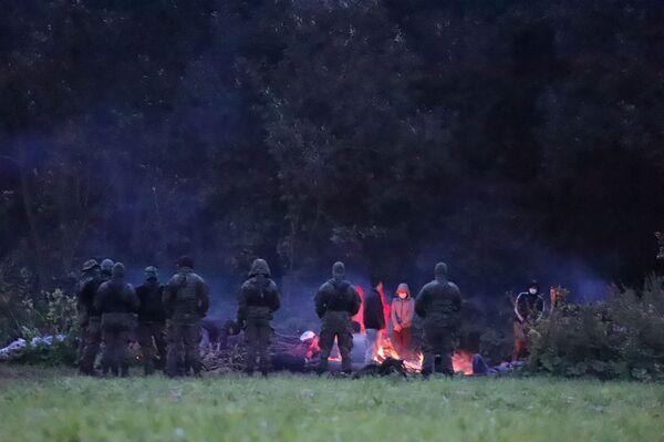 Polští pohraničníci střeží skupinu migrantů, kteří se pokusili překročit hranici mezi Běloruskem a Polskem poblíž vesnice Usnarz Gorny v Polsku - Sputnik Česká republika
