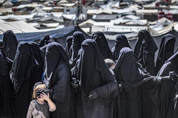 Ženy s dětmi stojí ve frontě na balíčky s humanitární pomocí v kurdském táboře Al-Hol v syrské provincii Hasaja, kde jsou drženi příbuzní údajných bojovníků skupiny Islámský stát (teroristická organizace zakázaná v Rusku) - Sputnik Česká republika