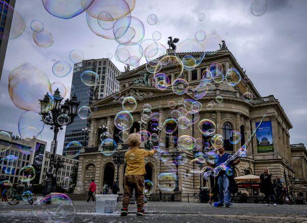 Chlapec si hraje s mýdlovými bublinami před Starou operou ve Frankfurtu nad Mohanem - Sputnik Česká republika
