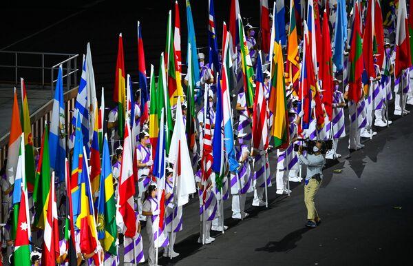 Dobrovolníci drží vlajky zúčastněných zemí během zahajovacího ceremoniálu XVI. letních paralympijských her - Sputnik Česká republika