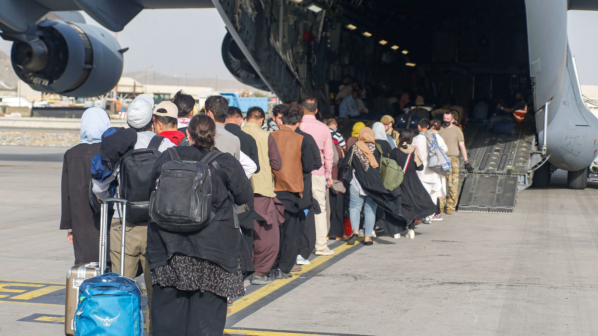 Afghánští uprchlíci při přistání letadla C-17 Globemaster III amerického letectva na mezinárodním letišti Hamída Karzáího v Kábulu - Sputnik Česká republika, 1920, 26.08.2021