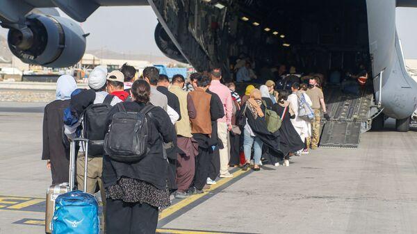 Афганские беженцы во время посадки на самолет C-17 Globemaster III ВВС США в международном аэропорту имени Хамида Карзая в Кабуле - Sputnik Česká republika