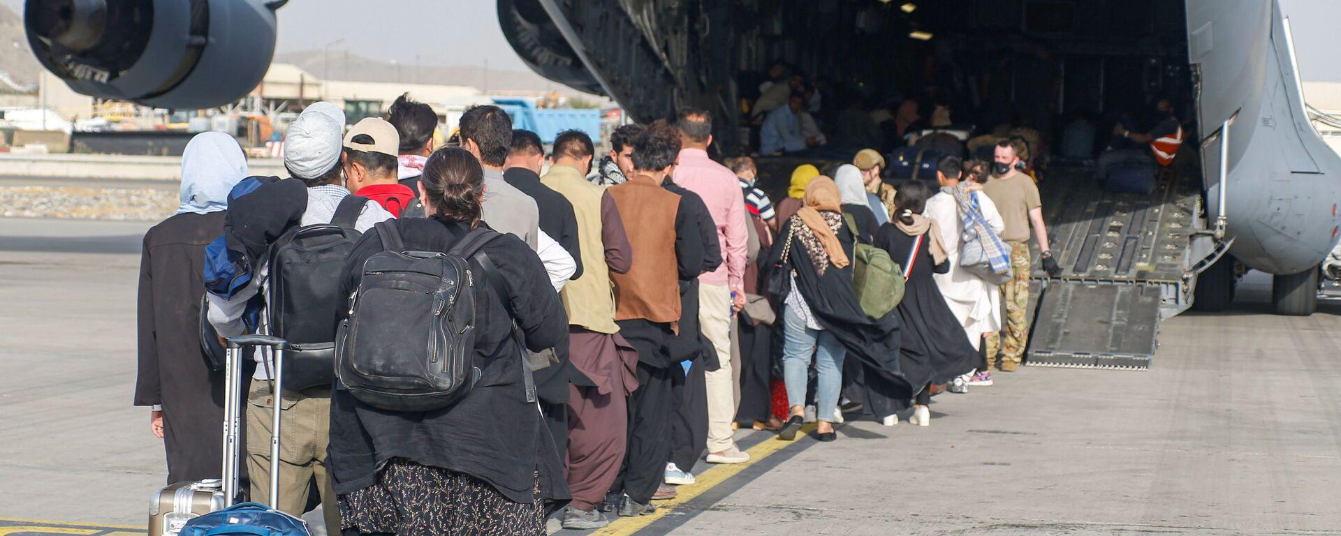 Afghánští uprchlíci při přistání letadla C-17 Globemaster III amerického letectva na mezinárodním letišti Hamída Karzáího v Kábulu - Sputnik Česká republika, 1920, 30.08.2021