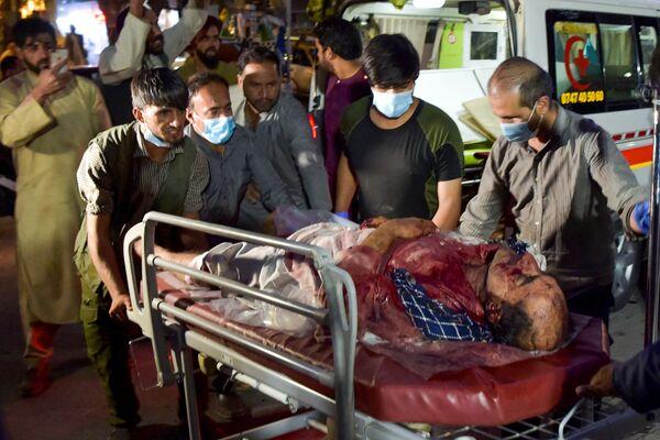 Zdravotníci a dobrovolníci poskytují pomoc zraněné osobě po teroristickém útoku v Kábulu. - Sputnik Česká republika