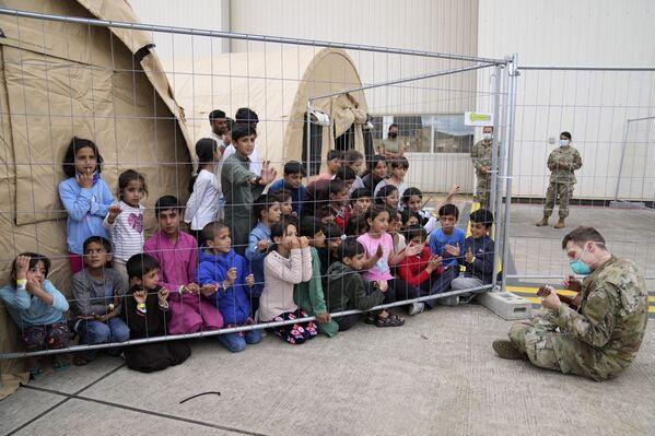 Americký voják hraje na kytaru pro evakuované děti na letecké základně USA v Německu. - Sputnik Česká republika
