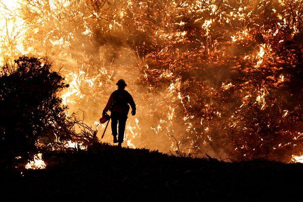 Hasič na pozadí požáru Caldor v Kalifornii. - Sputnik Česká republika
