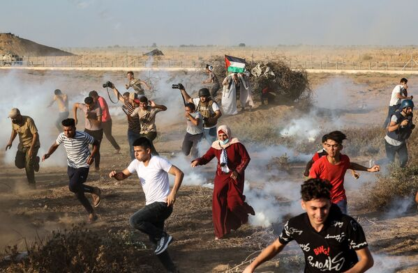Palestinští demonstranti a novináři utíkají před slzným plynem použitým izraelskými bezpečnostními složkami v Pásmu Gaza. - Sputnik Česká republika