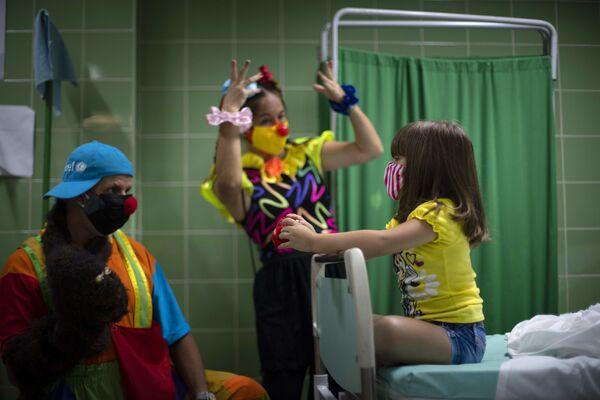 Klauni veselí holčičku poté, co absolvovala očkování vakcínou proti covidu-19. Havana, Kuba. - Sputnik Česká republika