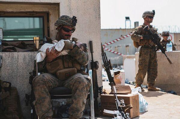 Americký voják drží miminko během evakuace z kábulského letiště. - Sputnik Česká republika