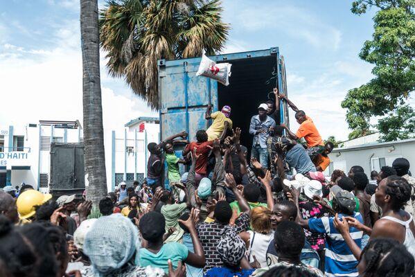 Rozdávání pytlů s rýží pro oběti zemětřesení na Haiti. - Sputnik Česká republika