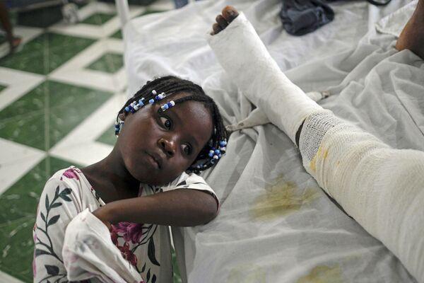 Dívka sedí vedle své matky zraněné při zemětřesení na Haiti. - Sputnik Česká republika