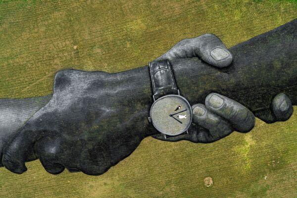 Na této fotografii, kterou vytvořil Valentin Flauraud v sobotu 14. března 2020, pracuje francouzsko-švýcarský umělec Saype (Guillaume Legrose) na sbírce šesti obřích biologicky rozložitelných landartových obrazech před bazilikou Notre-Dame de la Paix v Yamoussourko, Pobřeží slonoviny - Sputnik Česká republika