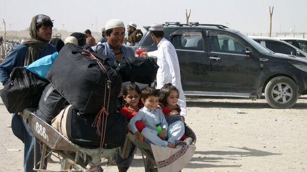 Afghánská rodina s věcmi na kontrolním stanovišti Brána přátelství v pákistánsko-afghánském pohraničním městě Chaman, Pákistán - Sputnik Česká republika
