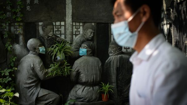 Мужчина проходит мимо скульптур в масках возле ресторана в Пекине - Sputnik Česká republika