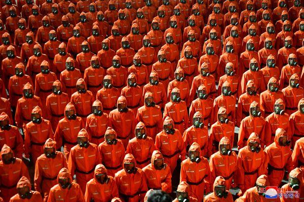 Personál v oranžových oblecích pochoduje během polovojenské přehlídky - Sputnik Česká republika