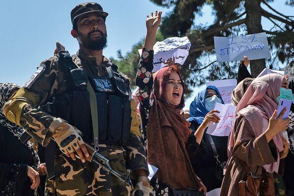 Afghánské ženy vykřikují protestní hesla vedle bojovníka Tálibánu během protipákistánské demonstrace poblíž pákistánského velvyslanectví v Kábulu. - Sputnik Česká republika