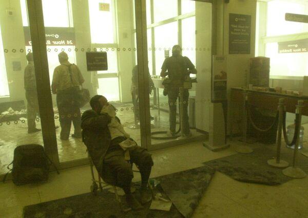 Zraněný muž čeká na pomoc, zatímco ostatní se uchylují do banky poblíž věží Světového obchodního centra 11. září 2001 v New Yorku - Sputnik Česká republika