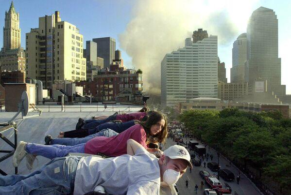 Lidé sledují ve středu 12. září 2001 ze střechy budovy na Greenwich St. v New Yorku, jak je ulice dole plná záchranářů a techniky - Sputnik Česká republika