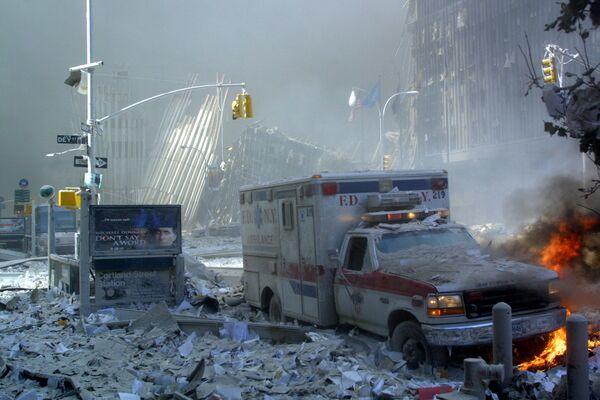 Poškozená sanitka a ulice pokrytá troskami po zřícení první budovy Světového obchodního centra v New Yorku - Sputnik Česká republika
