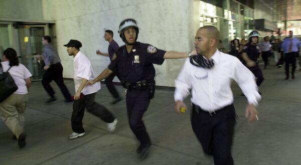 Lidé utíkají, když se zhroutí vrchol jedné z věží Světového obchodního centra poté, co 11. září 2001 v New Yorku narazila dvě letadla do severní a jižní věže - Sputnik Česká republika