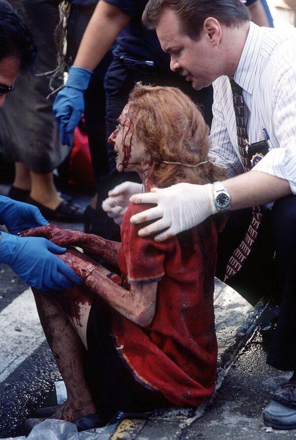 Záchranáři pomáhají ženě poté, co byla zraněna při teroristickém útoku na Světové obchodní centrum v New Yorku, 11. září 2001 - Sputnik Česká republika