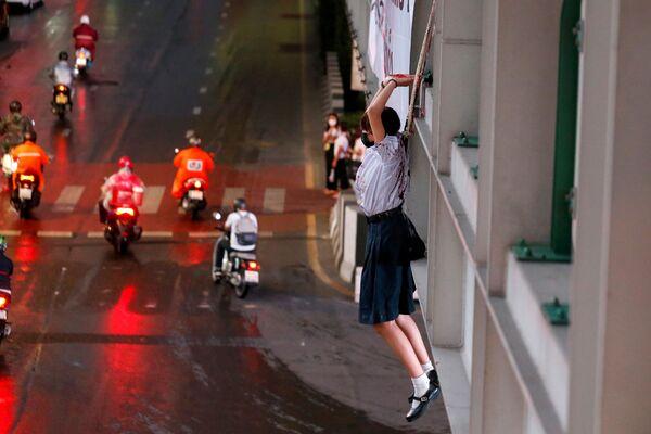 Demonstrantka napodobuje akt oběšení na protest proti covidovým opatřením thajské vlády.  - Sputnik Česká republika