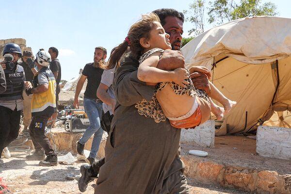Muž odnáší dívku, která byla zraněna při leteckém bombardování v provizorním táboře pro vysídlené Syřany. Město Kafraya, provincie Idlib. - Sputnik Česká republika