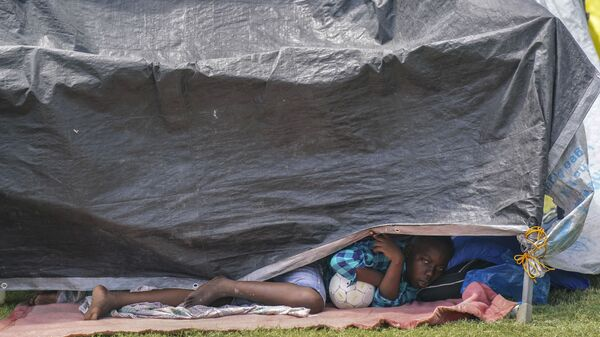 Ребенок в самодельной палатке в лагере беженцев для пострадавших от землетрясения в Ле-Ке, Гаити - Sputnik Česká republika
