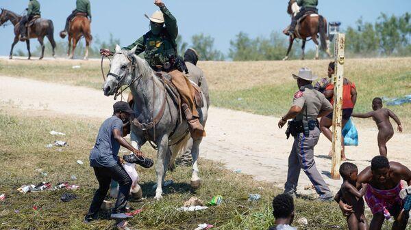 Пограничный патруль США на лошади пытается помешать гаитянскому мигранту войти в лагерь на берегу Рио-Гранде - Sputnik Česká republika