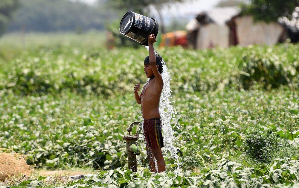 Chlapec se polévá vodou v hlavním městě Indie Novém Dillí.