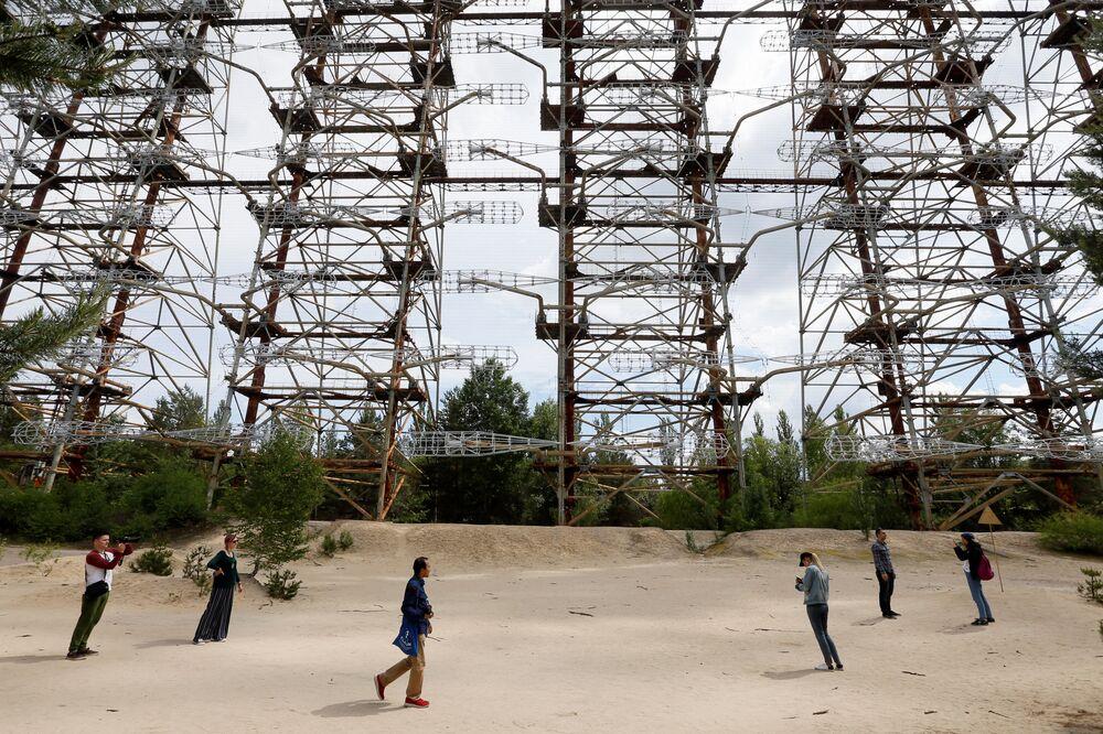 Turisté si prohlížejí opuštěný radarový systému Duga, který varoval před letem balistických raket.