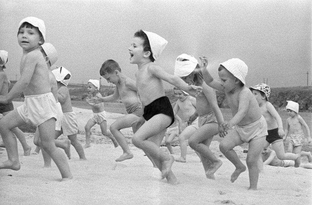 Chovanci mateřské školky běží po pláži v Dněpru, Ukrajinská SSR, 1966