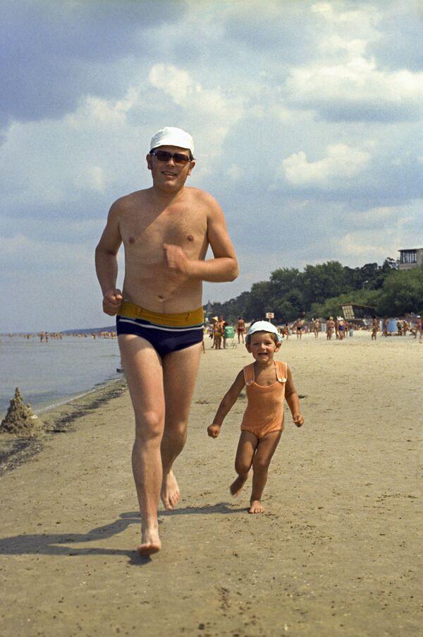 Táta a syn běží po pláži, Júrmala, Lotyšská SSR, 1975 - Sputnik Česká republika