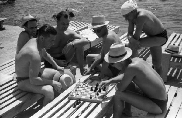 Na pláži sanatoria Ukrajina rekreanti hrají šachy, Jalta, 1958 - Sputnik Česká republika