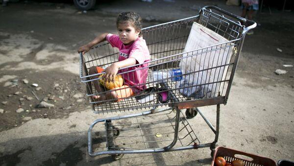 Dívka v nákupním vozíku ve venezuelském supermarketu - Sputnik Česká republika