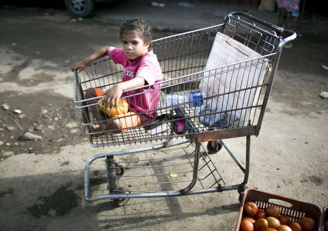 Dívka v nákupním vozíku ve venezuelském supermarketu