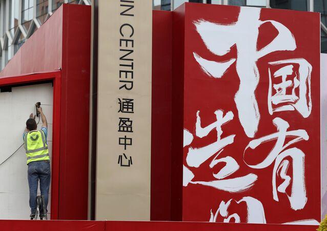 """Dělník instaluje reklamu """"Vyrobeno v Číně"""" (dne 8. května 2019). Americká cla proti Číně způsobila v dubnu propad čínského exportu."""