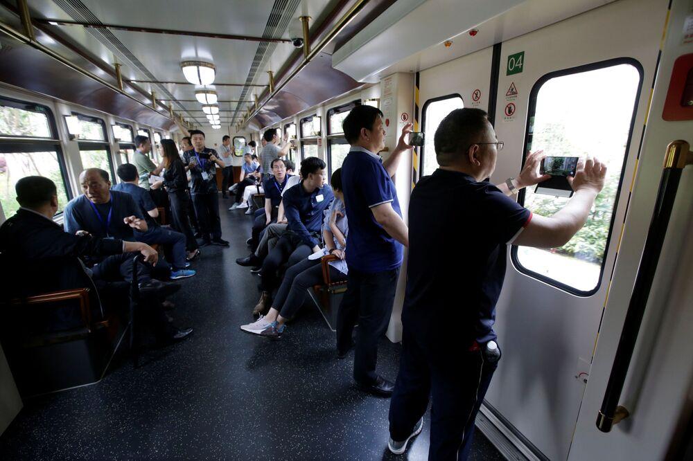 Návštěvníci kampusu Huawei si fotografují cestu vlakem.