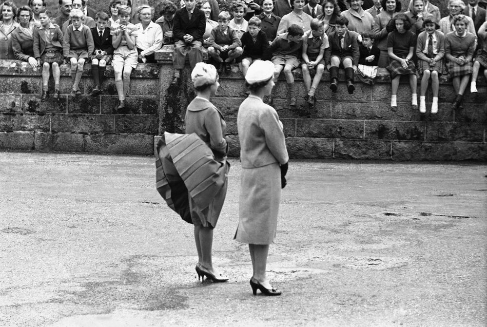 Vítr zvedá sukni princezny Margaret, zatímco spolu s královnou Alžebetou II. čekají na příchod amerického prezidenta Dwighta Eisenhowera na hrad Balmoral ve Skotsku, 28. srpna 1959.