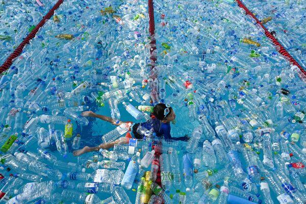 Dítě plave v bazénu naplněném plastovými lahvemi během informační kampaně na Světový den oceánů, Bangkok, Thajsko. - Sputnik Česká republika