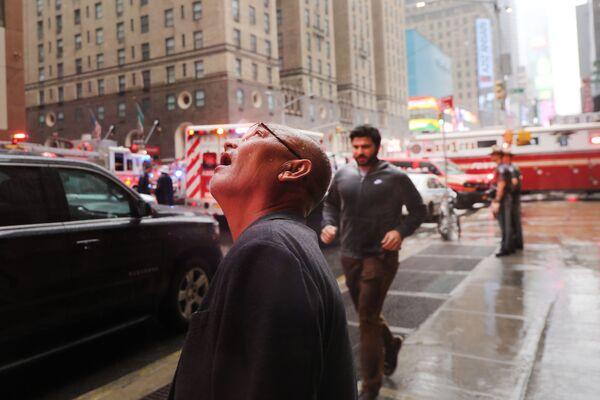 Muž sleduje místo havárie vrtulníku na mrakodrap v New Yorku. - Sputnik Česká republika