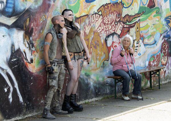 Dívky se fotí vedle zdi během každoročního Wave Gothic festivalu v Lipsku. - Sputnik Česká republika