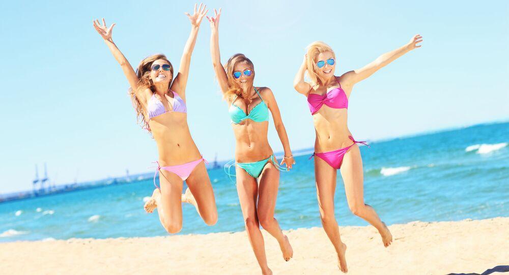 Dívky v plavkách na pláži.