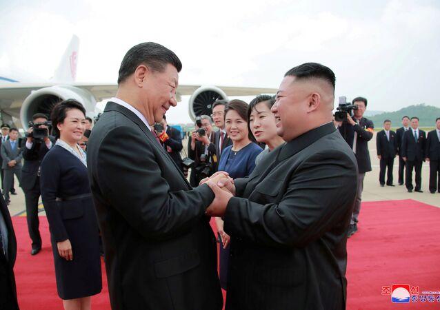 Severokorejský vůdce Kim Čong-un vítá čínského vedoucího představitele Si Ťin-pchinga na mezinárodním letišti v Pchjongjangu