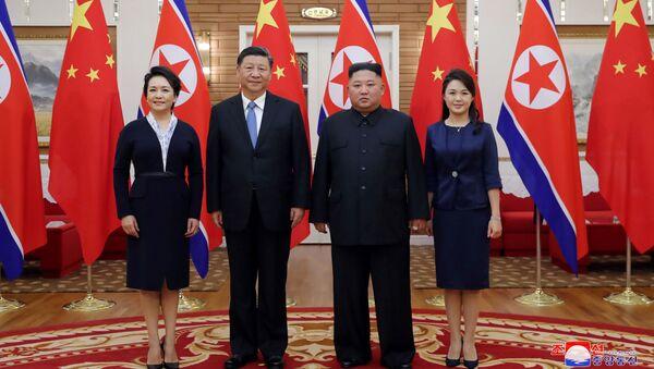 Vůdce KLDR Kim Čong-un a prezident Číny Si Ťin-pching spolu se svými manželkami Ri Sol-ču a Pcheng Li-jüan na schůzce v Pchjongjangu. - Sputnik Česká republika