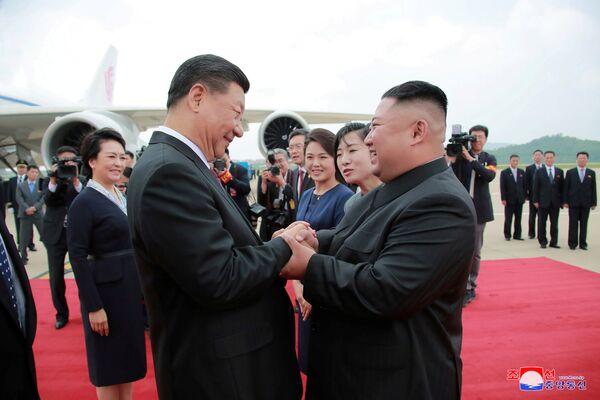 Severokorejský vůdce Kim Čong-un vítá čínského prezidenta Si Ťin-pchinga na letišti v Pchjongjangu. - Sputnik Česká republika