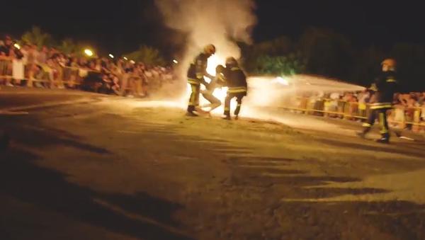 Mladí a starší Španělé skáčou přes táborák a často padají do ohně. Zachraňují je hasiči  (VIDEO)    - Sputnik Česká republika