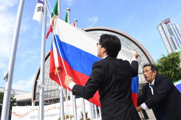 Organizátoři vztyčují ruskou vlajku před výstavištěm INTEX v Ósace, kde se konal summit G20. - Sputnik Česká republika